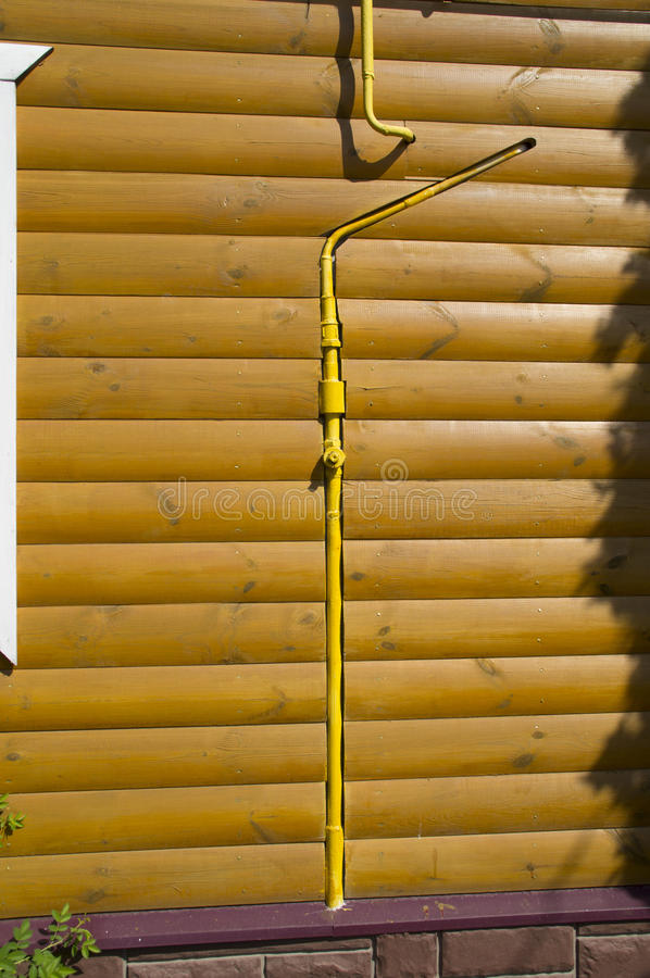 Wall of a wooden house and a gas pipeline stock photography
