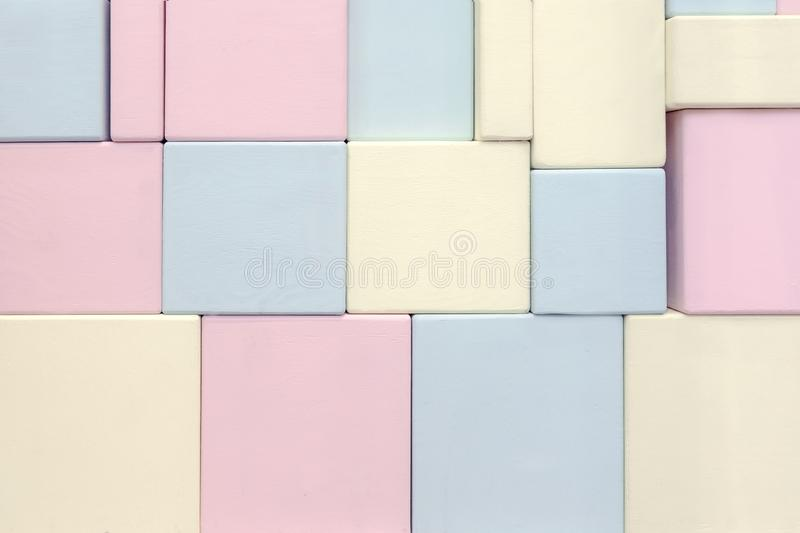 The wall of wooden rectangular shapes of different sizes of blue yellow and pink.  royalty free stock photo