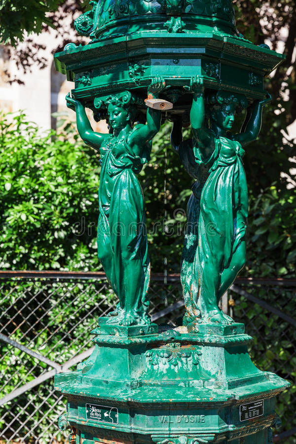 Wallace fountain with women sculpture on Montmartre hill. Paris, France. Paris, France - July 06, 2016: One of the drinking antique Wallace fountains with women stock image