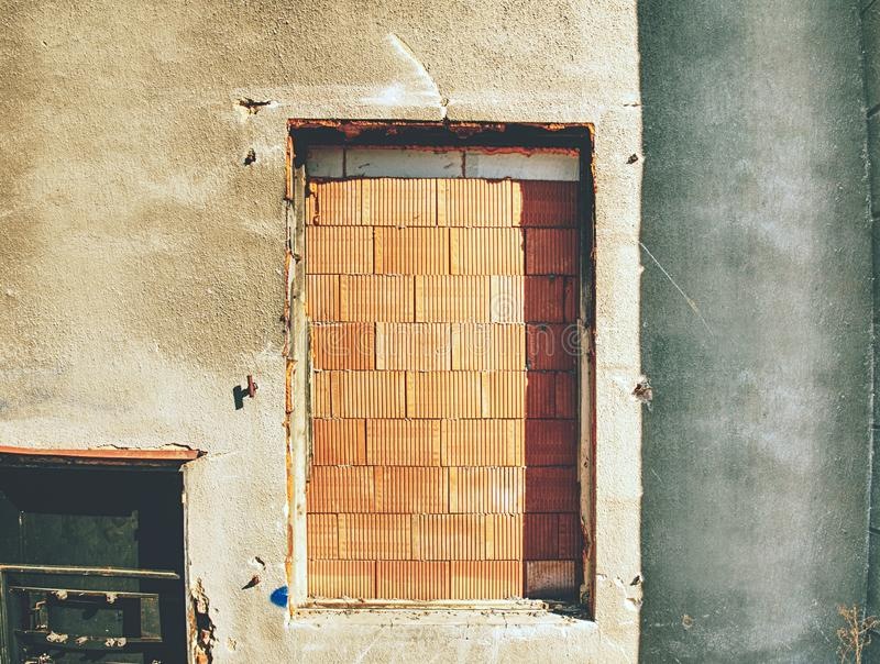 Walled door entry of abandoned house. Broken iron bars. Over door hole. Old weathered brick wall fragment stock photography