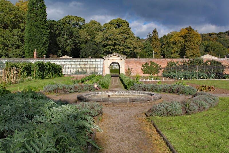 Walled kökträdgård med en bana och en rund springbrunn royaltyfri foto