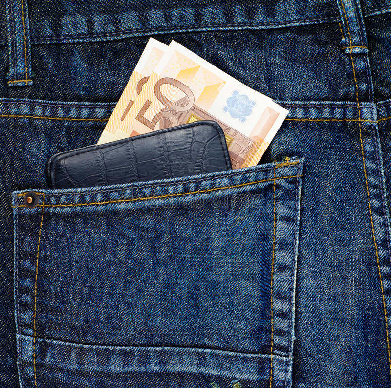Wallet in a back pocket of a jeans. Black wallet and euro bank notes in a back pocket of a navy blue denim jeans as a background composition royalty free stock photography