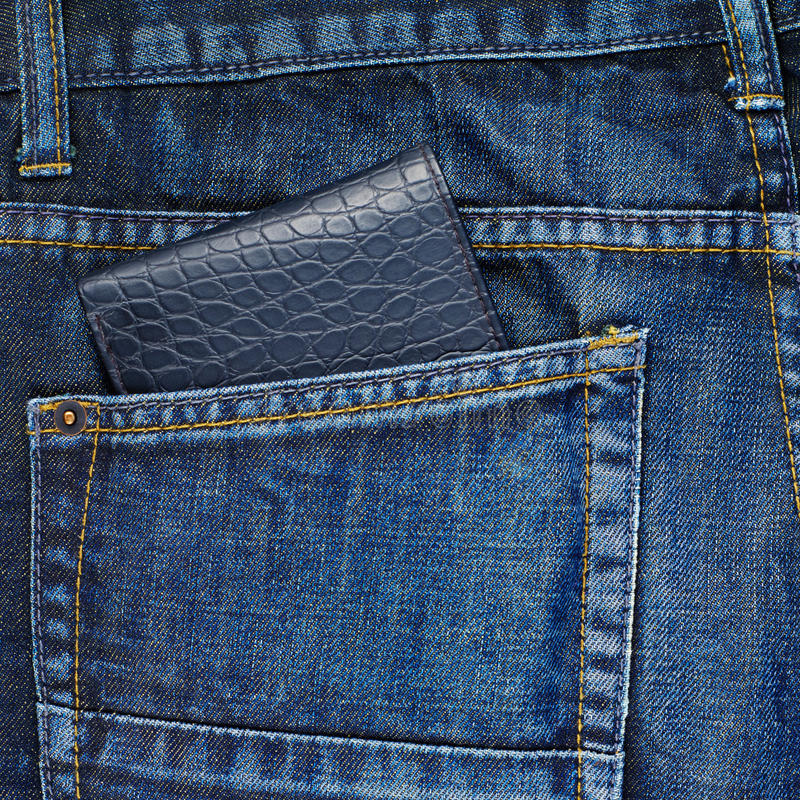 Wallet in a back pocket of a jeans. Black leather wallet in a back pocket of a navy blue denim jeans as a background composition stock image