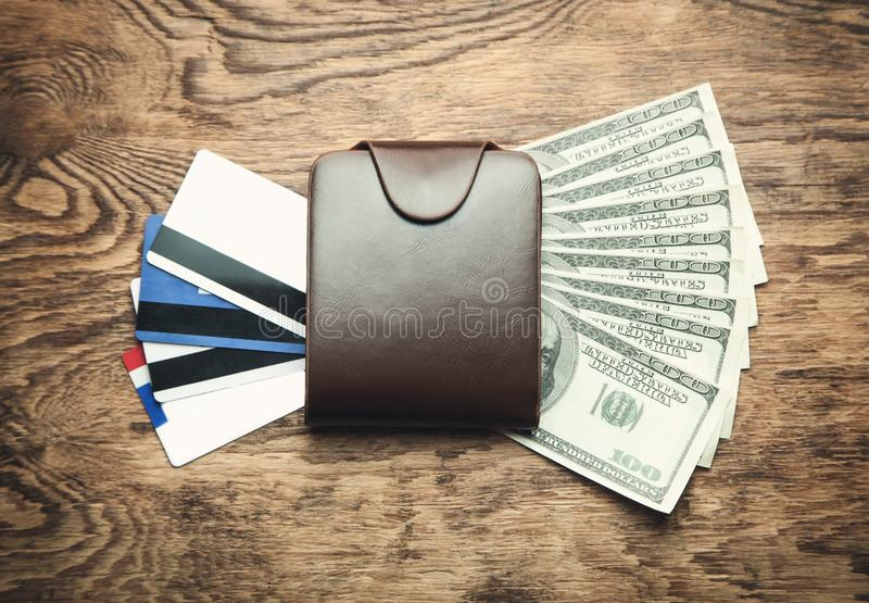 Wallet with credit cards and dollars on a wood background. royalty free stock image
