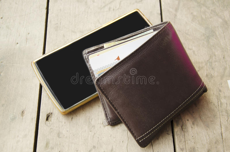 Wallet made from leather with smart phone. On wooden table stock photo