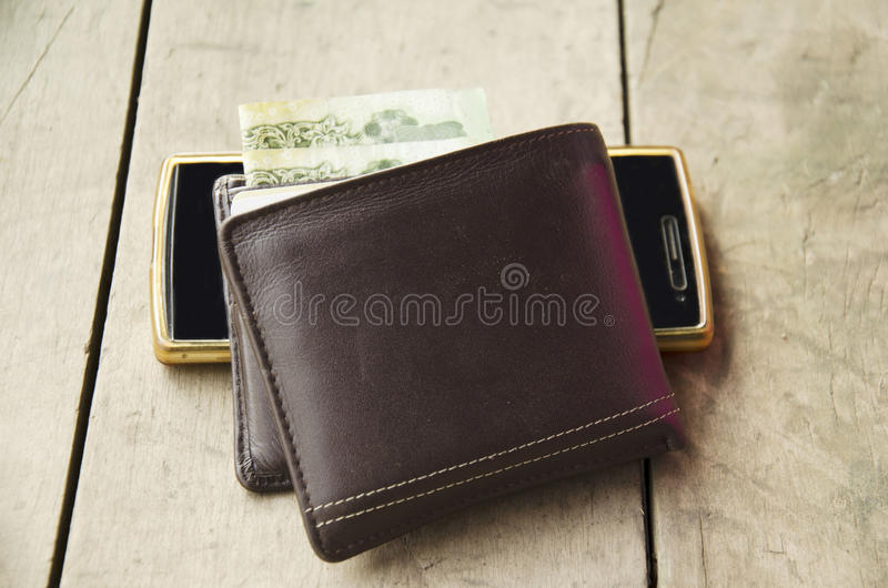 Wallet made from leather with smart phone. On wooden table royalty free stock image
