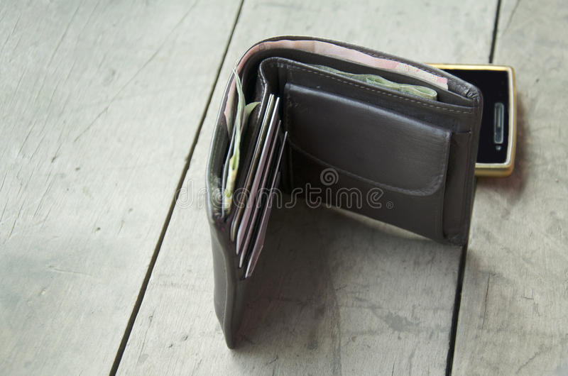 Wallet made from leather with smart phone. On wooden table royalty free stock photos