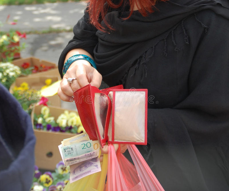 Wallet market. The young woman at the market pays in cash just bought flowers stock photo