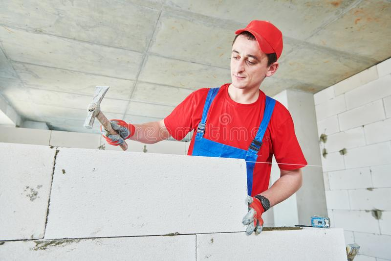 Walling. bricklayer installing autoclaved aerated concrete blocks. Bricklaying construction work or walling. bricklayer builder working with autoclaved aerated royalty free stock photos