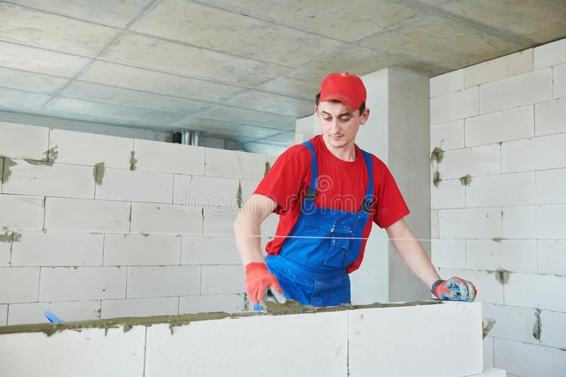 Walling. bricklayer installing autoclaved aerated concrete blocks. Bricklaying construction work or walling. bricklayer builder working with autoclaved aerated royalty free stock images