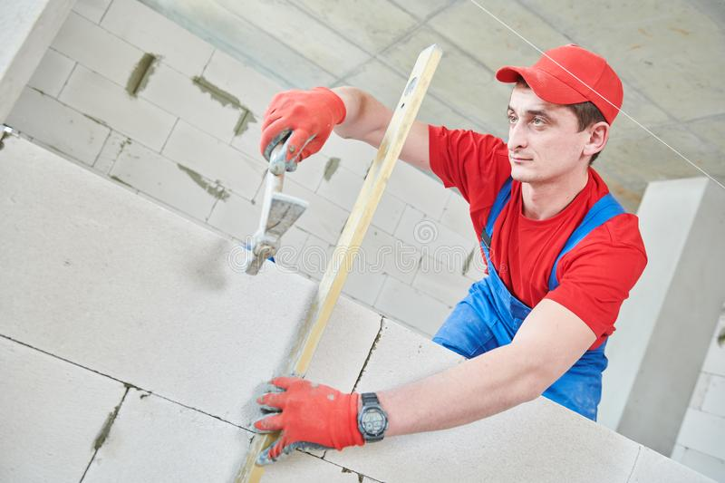Walling. bricklayer installing wall from autoclaved aerated concrete blocks. Bricklaying construction work or walling. bricklayer builder erecting wall from royalty free stock images