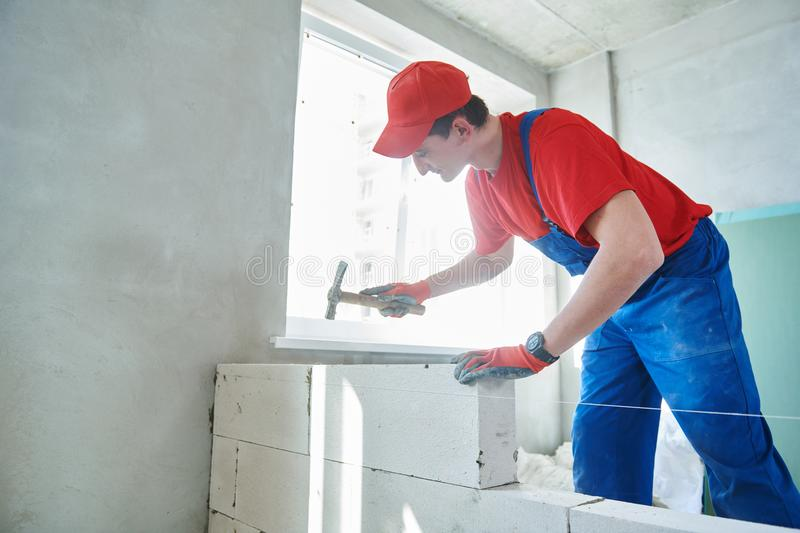 Walling. bricklayer installing wall from autoclaved aerated concrete blocks. Bricklaying construction work or walling. bricklayer builder erecting wall from stock photo