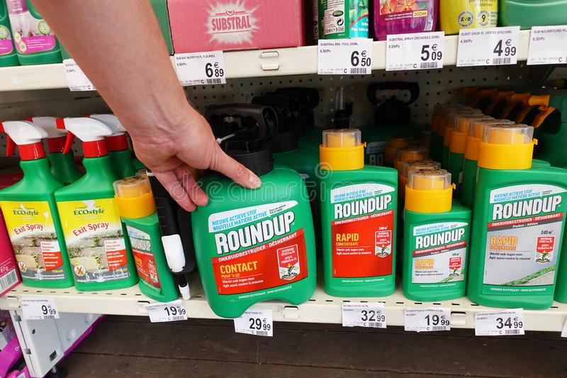 Roundup Weedkillers in a store. WALLONIA, BELGIUM - JULY 2019: Shelves with a variety of Herbicides in a Carrefour Hypermarket. Roundup is a brand-name of an royalty free stock photos