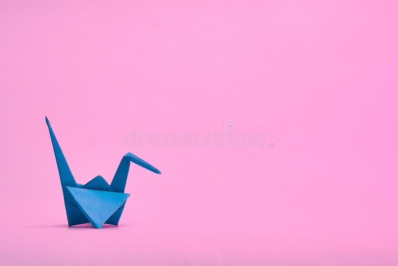 Wallpaper. Blue origami crane still life. Pink. Background stock photos