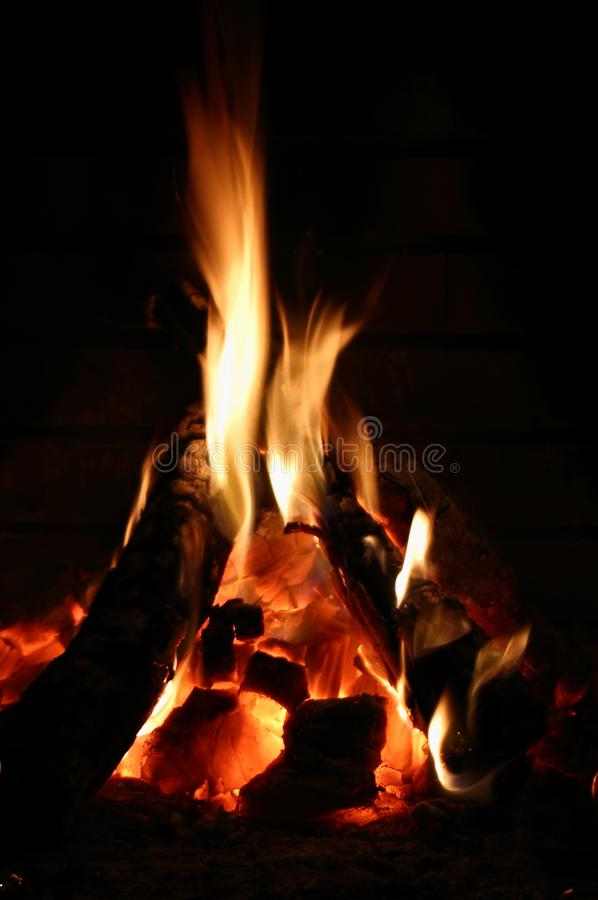 Wallpaper. Fire in fireplace. Black background. Fire fireplace on brick background. Strong contrast between the fire and the background. Colors: black, brown