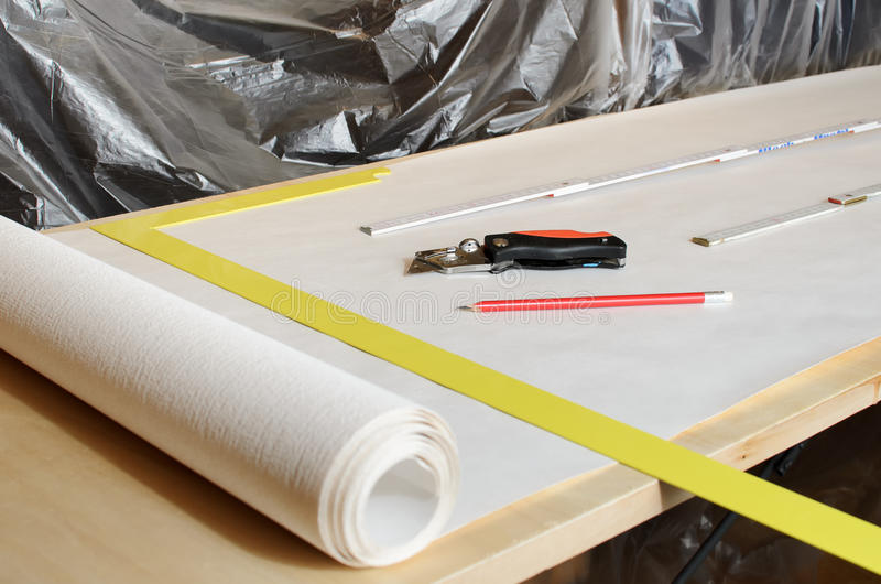Wallpaper. Measuring and cutting wallpaper at home royalty free stock photography