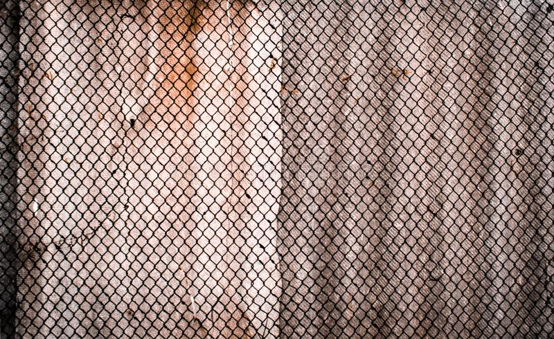 Wallpaper of old rusty metal grid, against a background of a concrete cement wall texture royalty free stock image
