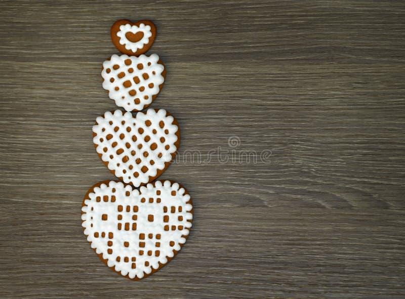 Wallpaper para el artilugio de la tableta con las galletas en forma de corazón con la formación de hielo en un fondo de madera imagen de archivo