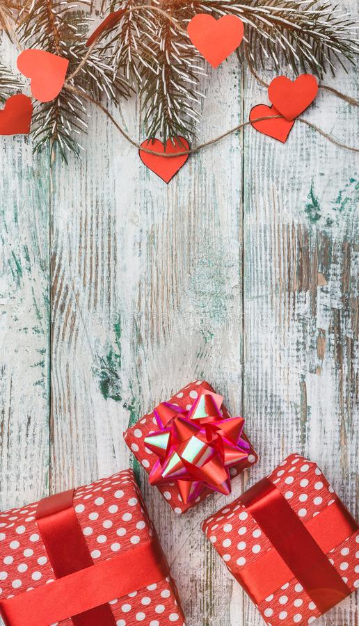 Wallpaper of white wood, vertical. Fir tree with hearts and red gifts. Space for wishes with winter, xmas, New Year and Christmas. Effect of light blips. Top royalty free stock photos