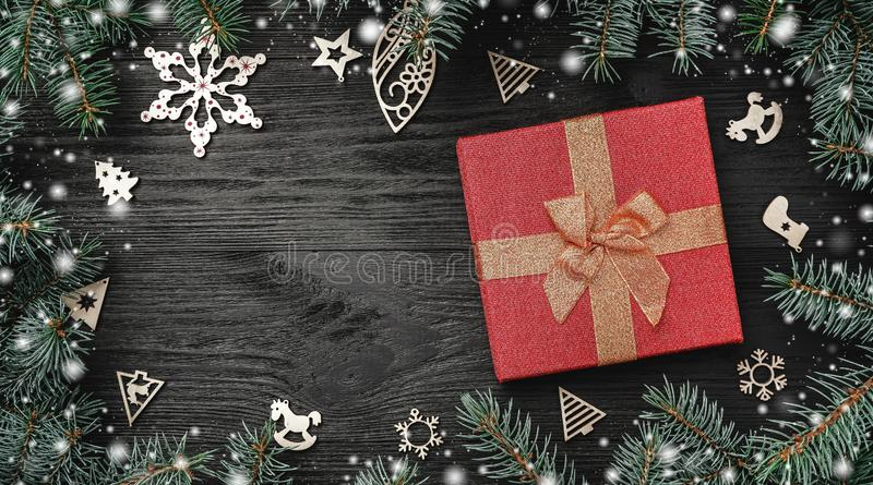 Wallpaper of winter holidays on black background. Red gift and wooden toys. Fir trees around. Top view. Xmas greeting card. With snow effect royalty free stock image