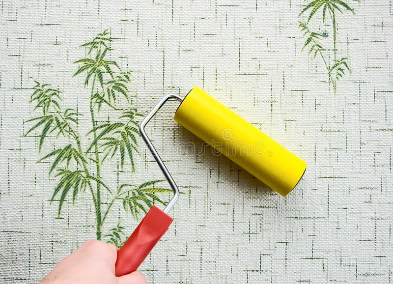 Wallpapering. With roller to remove air stock photos