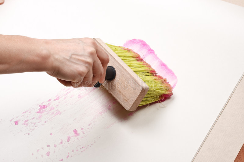 Wallpapering. The hand smearing wall-paper by glue. Home renovation royalty free stock image
