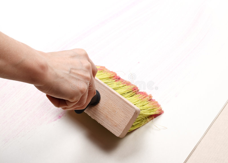 Wallpapering. The hand smearing wall-paper by glue. Home renovation royalty free stock photo