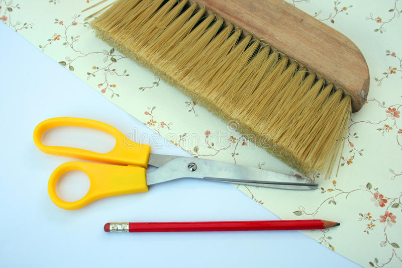 Wallpapering tools. Wallpapering brush with scissors and a pencil on a sheet of patterned wallpaper royalty free stock photography