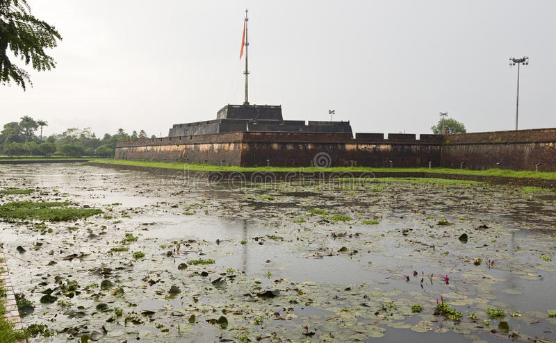 Walls of the Citadel in Hue. The Vietnamese flag hangs atop the giant flagpole above the ancient walls of the citadel in Hue on a rainy day stock photo