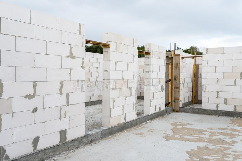 The walls of a house built of white brick with reinforced concrete pillars at the end of which there are ribbed rods, wooden formw. Ork visible from the pillars stock photos