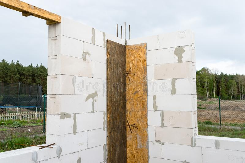 The walls of a house built of white brick with reinforced concrete pillars at the end of which there are ribbed rods, wooden formw. Ork visible from the pillars stock photography