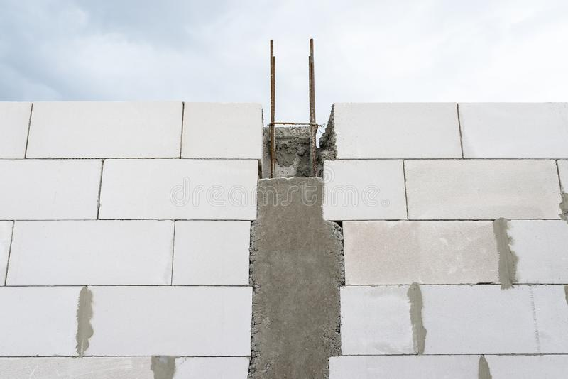 The walls of a house built of white brick with reinforced concrete pillars at the end of which there are ribbed rods, wooden formw. Ork visible from the pillars royalty free stock photography