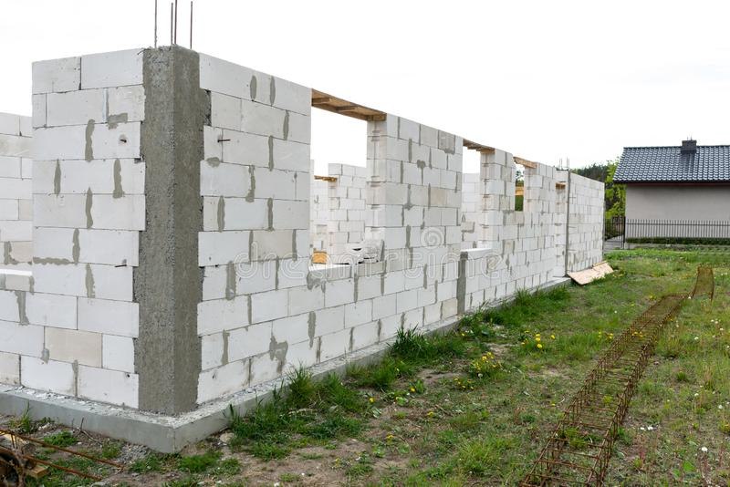 The walls of a house built of white brick with reinforced concrete pillars at the end of which there are ribbed rods, wooden formw. Ork visible from the pillars royalty free stock photos