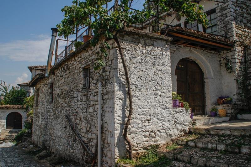The walls, house and stone road in the historic white town below the fortress. The common life of the Albanian UNESCO World Heritage Site stock photography