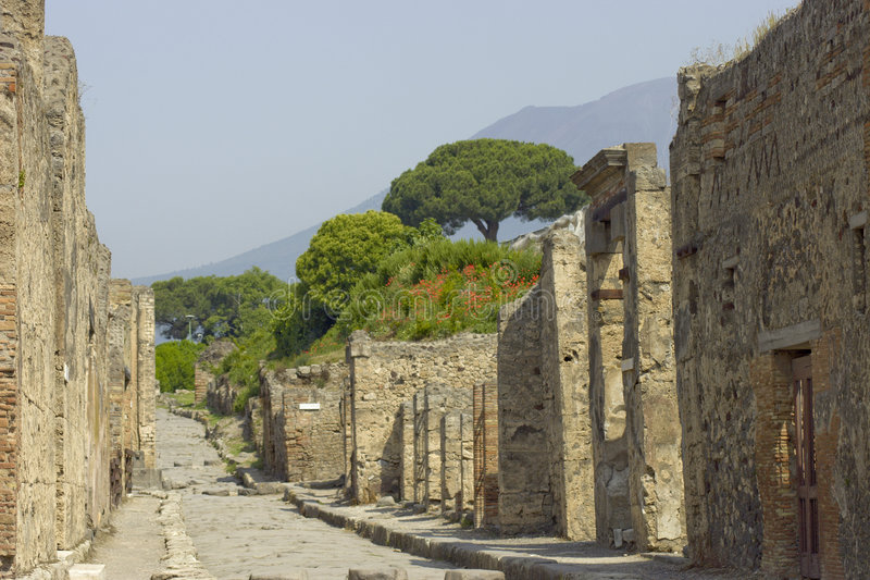 Walls of Pompeii. Stone walls stand among the ruins of the ancient Italian city of Pompeii, with Mount Vesuvius looming in the background stock photo