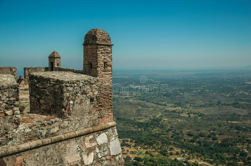 Walls and watchtowers in stronghold at the Marvao Castle. Stone walls and watchtowers in stronghold over cliff next to Castle, with hilly landscape on sunny day royalty free stock photo