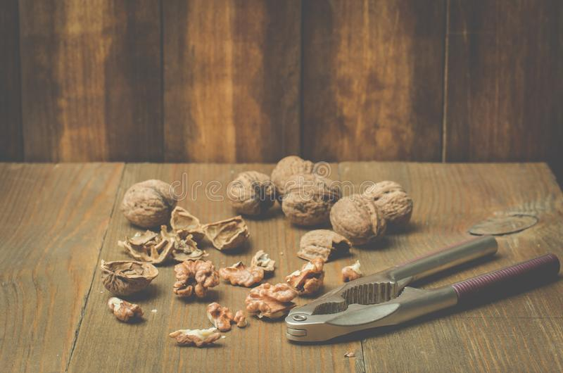 walnut Ένα κοχύλι και ένας καρυοθραύστης σε έναν ξύλινο πίνακα στοκ φωτογραφίες