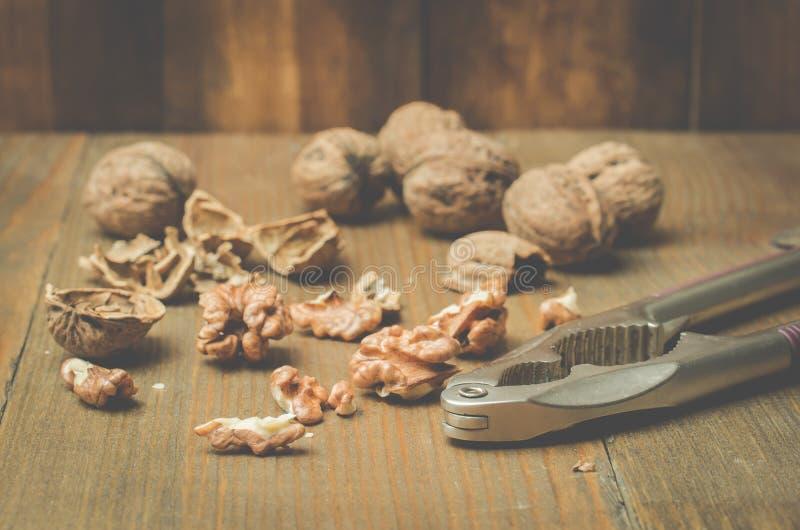 walnut Ένα κοχύλι και ένας καρυοθραύστης σε έναν ξύλινο πίνακα στοκ φωτογραφία με δικαίωμα ελεύθερης χρήσης