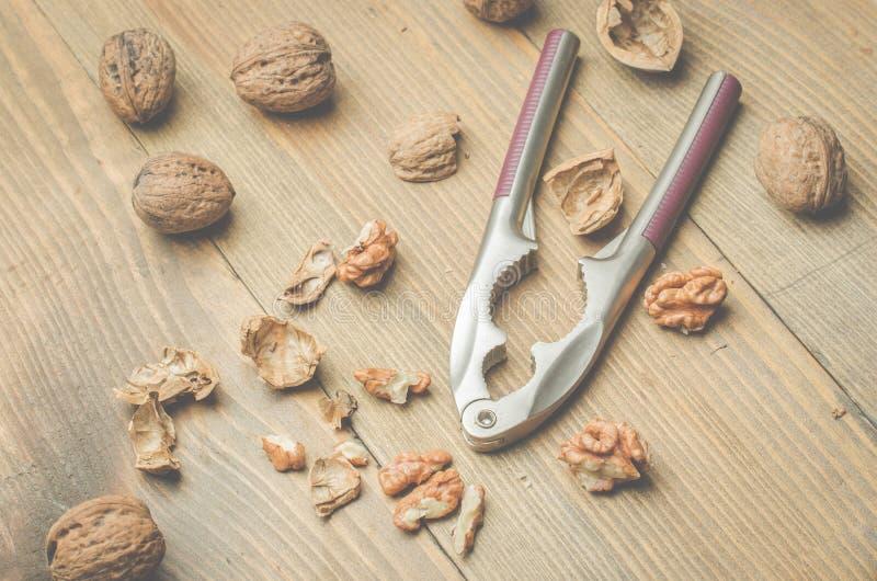 walnut Ένα κοχύλι και ένας καρυοθραύστης σε έναν ξύλινο πίνακα r στοκ φωτογραφία με δικαίωμα ελεύθερης χρήσης