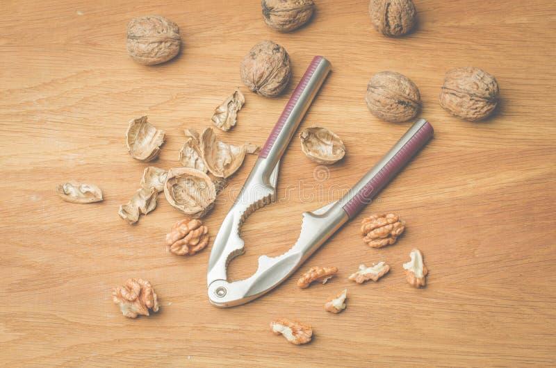 walnut Ένα κοχύλι και ένας καρυοθραύστης σε ένα ξύλινο υπόβαθρο r στοκ φωτογραφία
