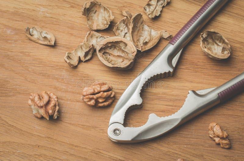 walnut Ένα κοχύλι και ένας καρυοθραύστης σε ένα ξύλινο υπόβαθρο r στοκ εικόνα με δικαίωμα ελεύθερης χρήσης