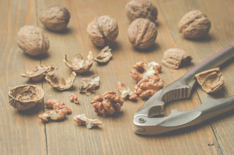 walnut καρυοθραύστης και το διασπασμένο ξύλο καρυδιάς σε έναν ξύλινο πίνακα στοκ εικόνες