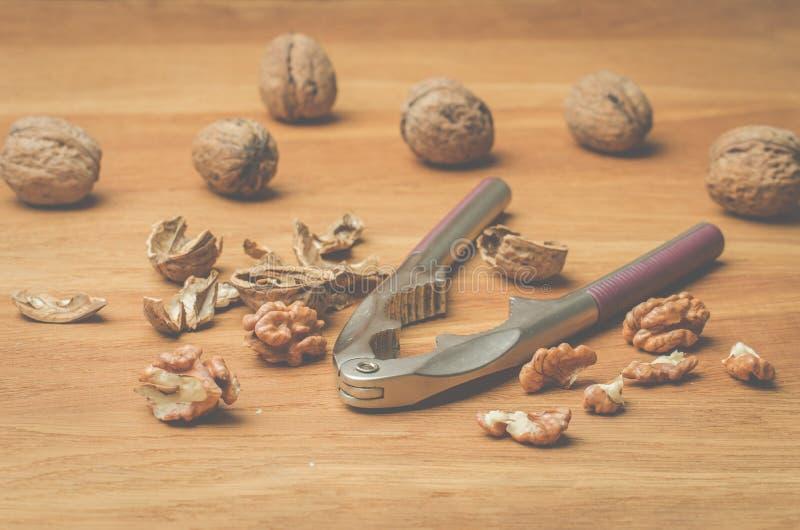 walnut καρυοθραύστης και το διασπασμένο ξύλο καρυδιάς σε έναν ξύλινο πίνακα στοκ φωτογραφίες με δικαίωμα ελεύθερης χρήσης