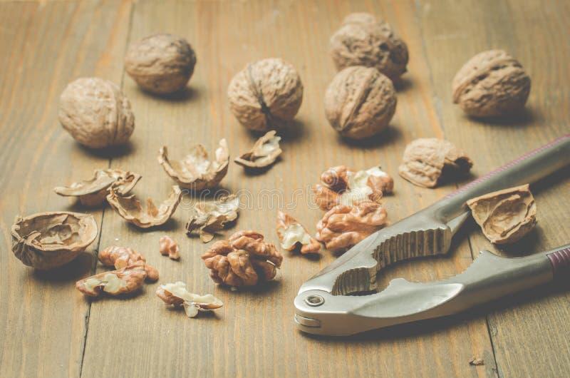 walnut καρυοθραύστης και το διασπασμένο ξύλο καρυδιάς σε ένα ξύλινο υπόβαθρο στοκ φωτογραφία με δικαίωμα ελεύθερης χρήσης