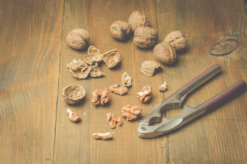 walnut καρυοθραύστης και το διασπασμένο ξύλο καρυδιάς σε ένα ξύλινο υπόβαθρο στοκ φωτογραφία