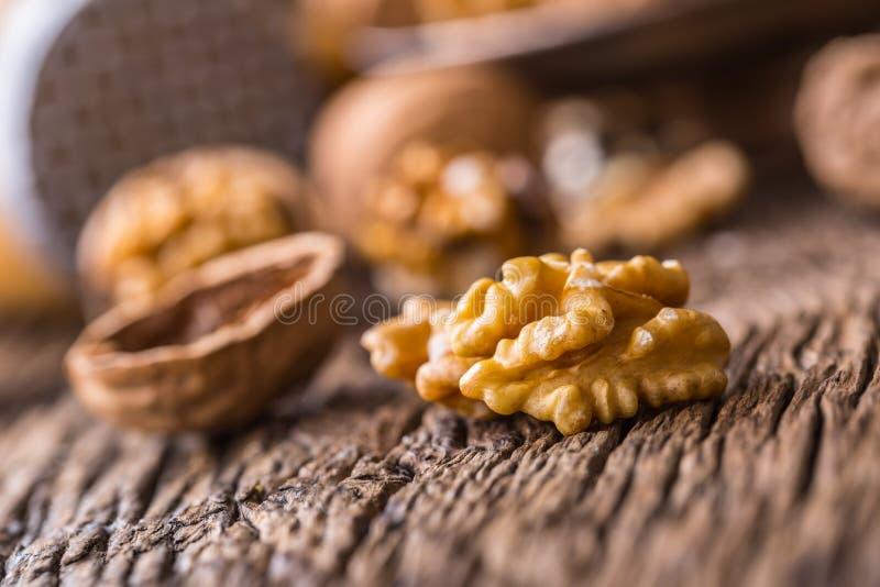 walnut Πυρήνες ξύλων καρυδιάς και ολόκληρα ξύλα καρυδιάς στον αγροτικό παλαιό δρύινο πίνακα στοκ εικόνα