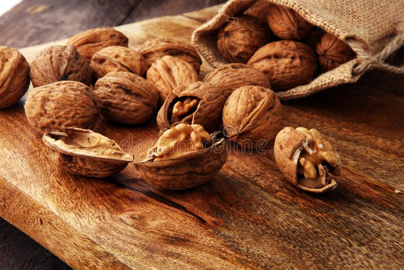 walnut Πυρήνες ξύλων καρυδιάς και ολόκληρα ξύλα καρυδιάς burlap στο σάκο στοκ εικόνα με δικαίωμα ελεύθερης χρήσης