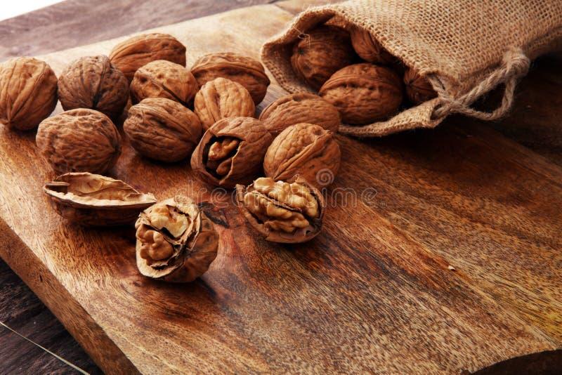 walnut Πυρήνες ξύλων καρυδιάς και ολόκληρα ξύλα καρυδιάς burlap στο σάκο στοκ εικόνα