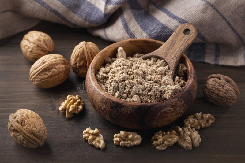 Walnut flour in the wooden bowl stock images