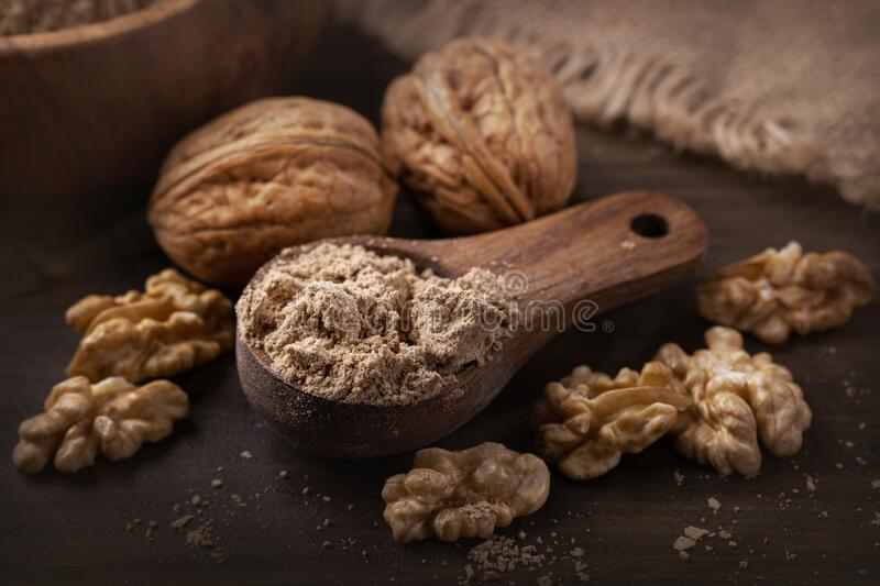 Walnut flour in the wooden spoon royalty free stock photo